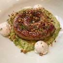 Grilled lamb sausage with green pea hummus