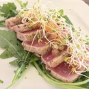 Tuna Steak with a sweet middle of red ringed by seasoned seared sides.