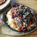 Bacon mushroom baked rice, creamy and well-charred by the pan.