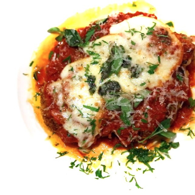 Veal Chop Parmigiana with classic red sauce, melting mozzarella.