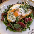 Saute green peas with shaved jamon & a fried egg