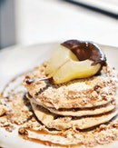 Scrumptious 🥞🍐 EARL GREY PANCAKES WITH POACHED PEAR  Unique and still one of Punch's most prominent dish are it's earl grey flavoured pancakes topped with macadamia crumbles and a half coated chocolate poached pear.