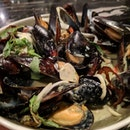 A bowl filled with mussels and Thai green curry.