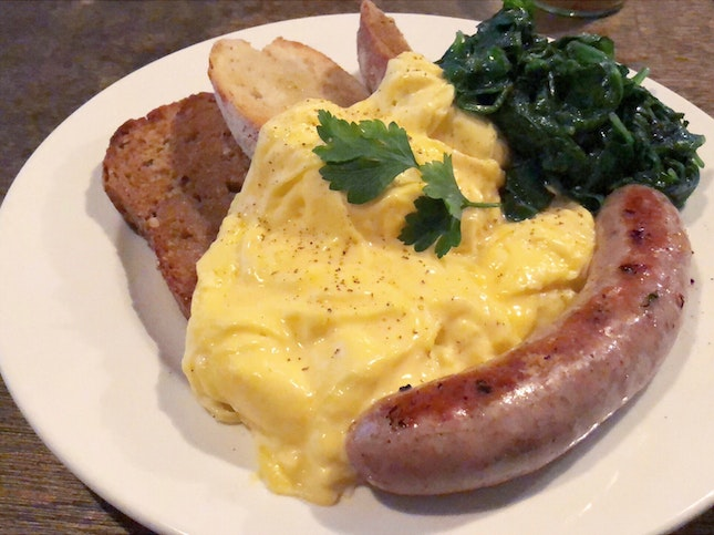 Scrambled Eggs on Toast with Pork Sausage and Wilted Spinach
