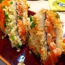 """Sushi Sandwich--A unique rice """"sandwich"""" that's been lightly toasted, giving this dish a nice crispy crunch as you sink your teeth into the spicy tuna and salmon combination within."""