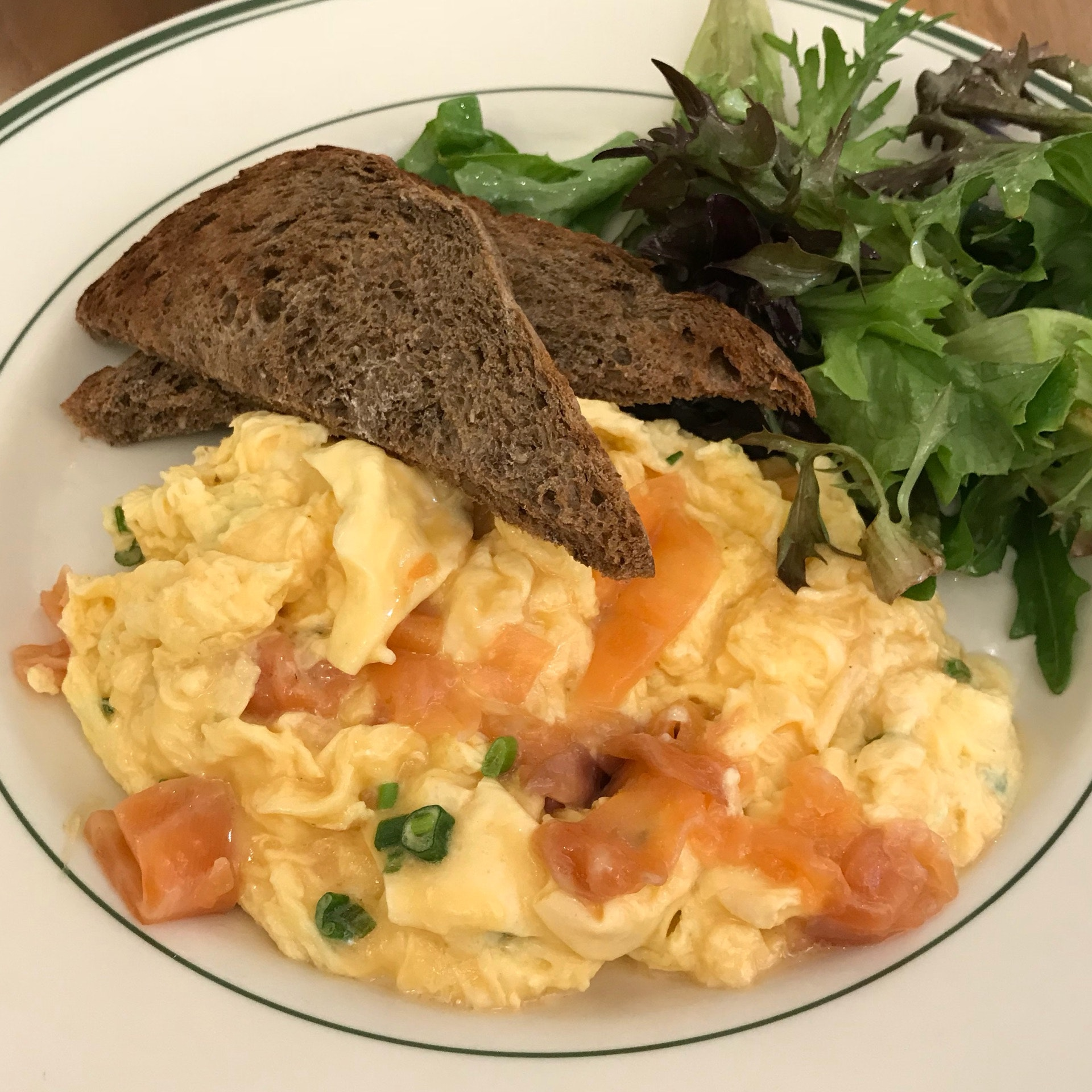 Smoked Salmon Scramble [23.00] soft scrambled eggs, house-smoked salmon, scallion cream cheese, with dressed greens