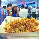 Bjorn Shen's Khao Soi Hotdog; chicken sausage hotdog drizzled with red curry mayo, pickled vegetables and topped with crispy noodle bits.