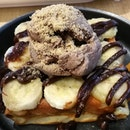 Average tasting piece of waffle with sliced bananas and a scoop of bland rocher ice cream