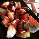 Grilled octopus on a bed of potatoes.