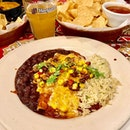 Beef Enchilada - 3 baked beef enchiladas topped with ancho sauce, melted cheese, chopped cilantro and house-made corn and black bean salsa with citrus-chile rice and black beans.