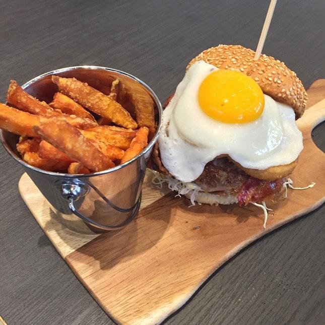 Nido Homemade Pork Burger ($18.90) — 150g pork patty, bacon, fried egg, onion rings, with sweet potato fries