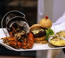 The Surf and Turf Welcome Platter that comes with Black Pepper Crab in a Bucket, Jumbo Clam Gratin and Beef Slider.