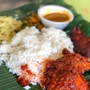 Traditional Indian food served on a banana leaf.