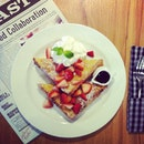 French toast with strawberries whip cream and maple syrup!